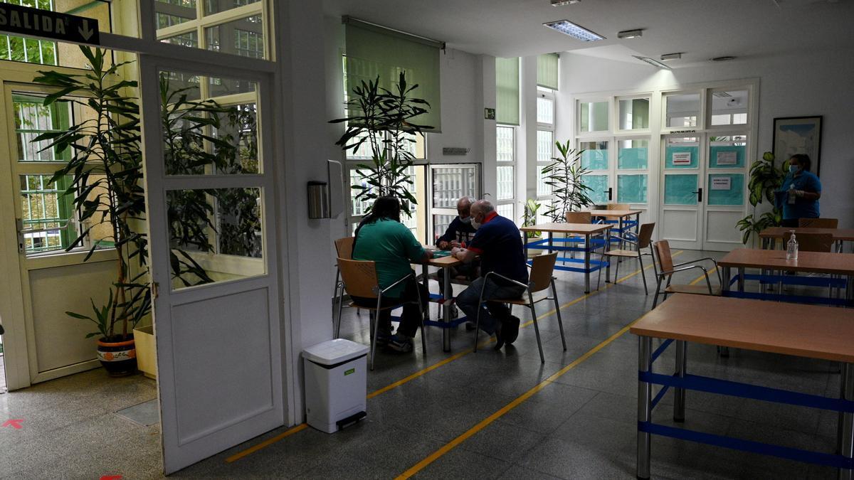 Un grupo de ancianos juega a las cartas en un centro de mayores en Madrid