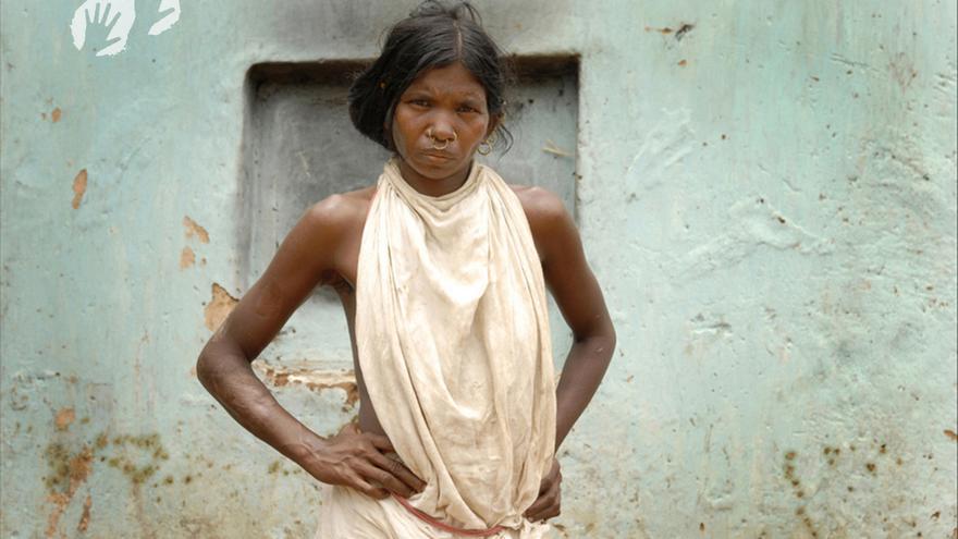 """Ser una mujer dongria kondh de las colinas de Niyamgiri en el estado de Odisha, en la India, es estar íntimamente conectada con tu tierra. Llevan milenios viviendo prósperamente en las frondosas colinas boscosas, con sus arroyos perennes y los gigantescos árboles de yaca. Se llaman a sí mismas jharnia, que significa protectoras de los arroyos. Durante los últimos diez años las mujeres dongria kondhs han trabajado codo con codo con los hombres drongrias para proteger a Niyamgiri de los devastadores planes de Vedanta Resources para construir una mina de bauxita a cielo abierto en su montaña más sagrada, Niyam Dongar, la """"montaña de la ley"""". Una de sus acciones fue formar una cadena humana alrededor de la base de la montaña para evitar que las excavadoras de Vedanta la destruyeran. En agosto de 2013, los dongria kondhs rechazaron por mayoría absoluta la apertura de una mina a cielo abierto de bauxita, del gigante minero británico Vedanta Resources, en su montaña sagrada. Esto supone un triunfo sin precedentes para los derechos indígenas.  Muchos de los dongrias más representativos, aquellos que han protestado públicamente y han viajado 1.600 km hasta Delhi, exigen que la policía libere a los líderes que permanecen detenidos, entre los que también hay mujeres. No entregaremos a nadie nuestros bosques, dijo una mujer dongria. Todas las mujeres están dispuestas a ir a la cárcel por esto. En enero de 2014, su persistencia dio resultados: el Gobierno de la India anunció que la mina no sería aprobada./©Jason Taylor"""