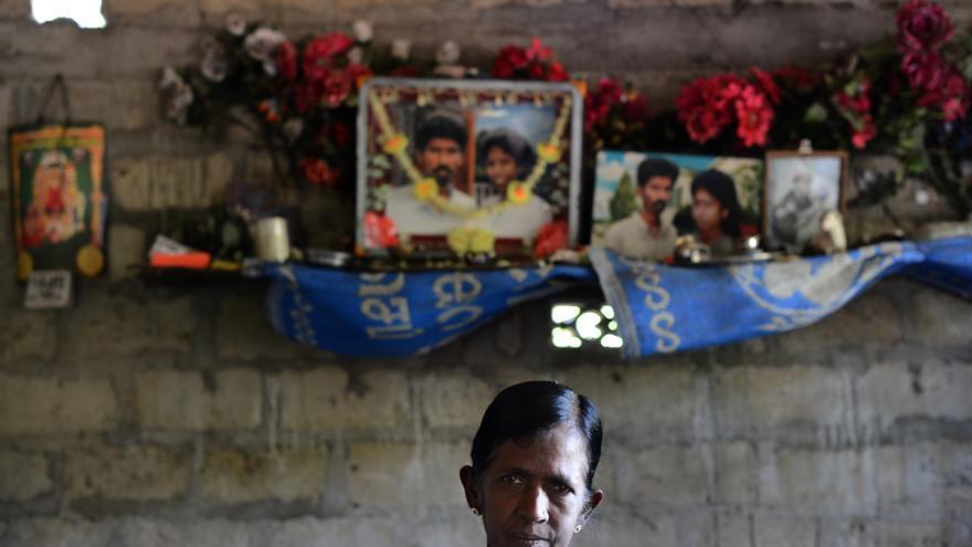 Soba Kunarathiram posa frente al altar en el que se recuerda a su esposo, asesinado por tropas cingalesas. Desde entonces sufre problemas cardíacos que le impiden trabajar. Sobrevive en Kilinochchi gracias a las clases de informática que da su hija. Fotografía: Zigor Aldama