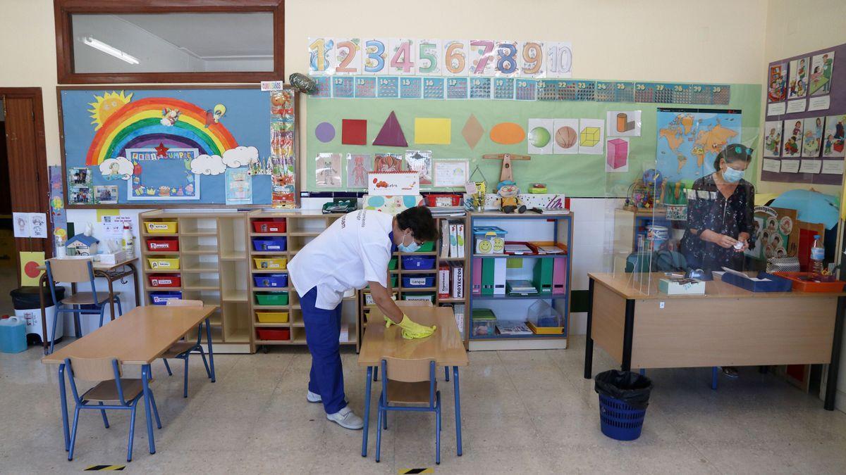 Una limpiadora desinfecta un aula