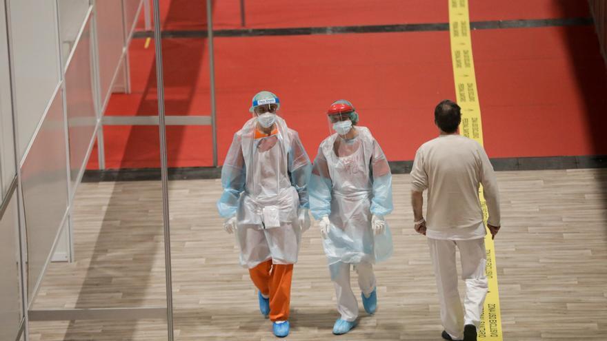 Trabajadores sanitarios protegidos caminan por el interior del hospital de campaña montado en IFEMA.