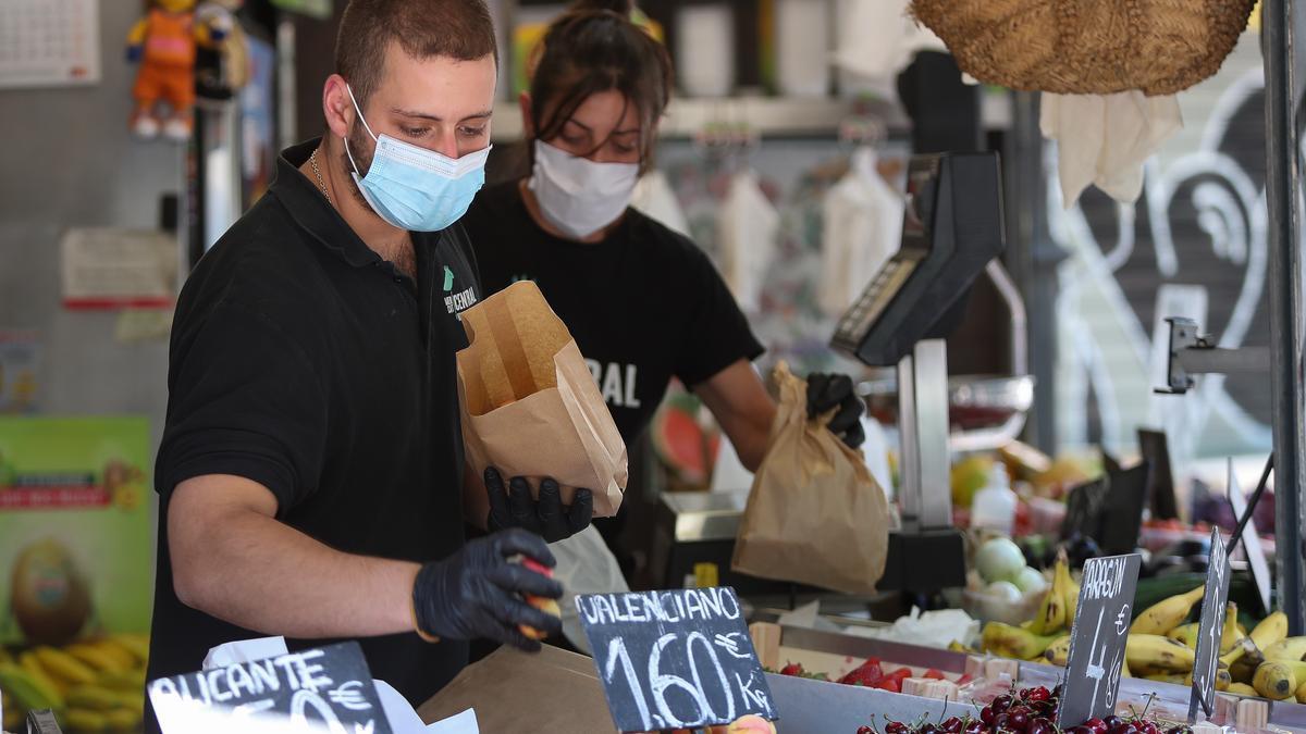 Dos trabajadores de una frutería del Mercado Central de Valencia