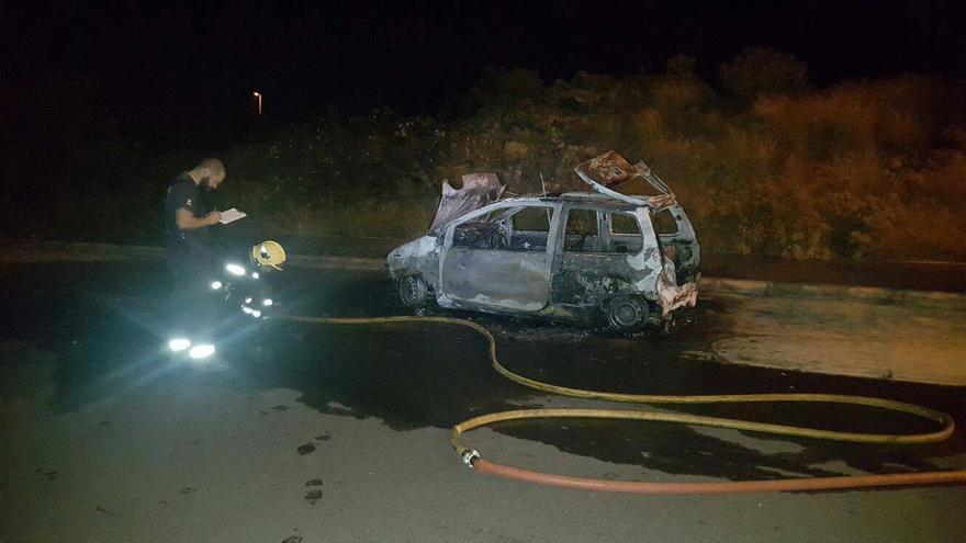 En la imagen, dos bomberos y el vehículo calcinado. Foto: BOMBEROS LA PALMA.
