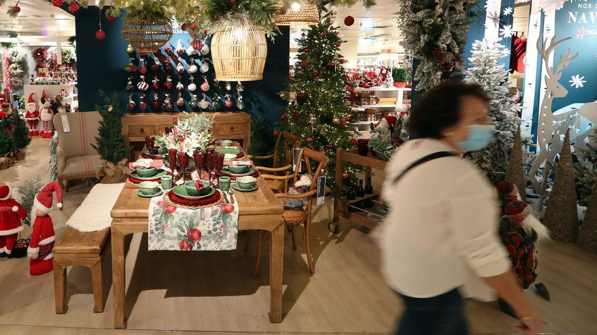 Una mujer pasea por una tienda con decoración navideña.