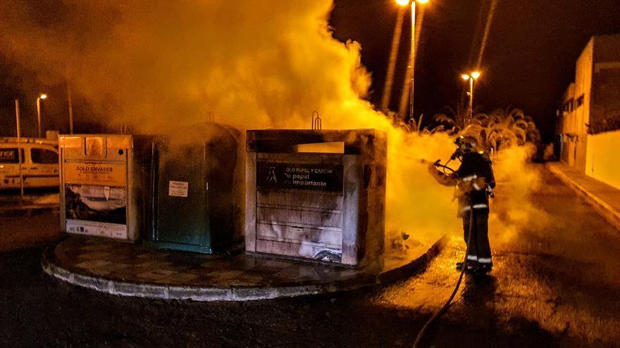 Intervención de un bombero en el incendio de un contenedor de residuos en El Paso.