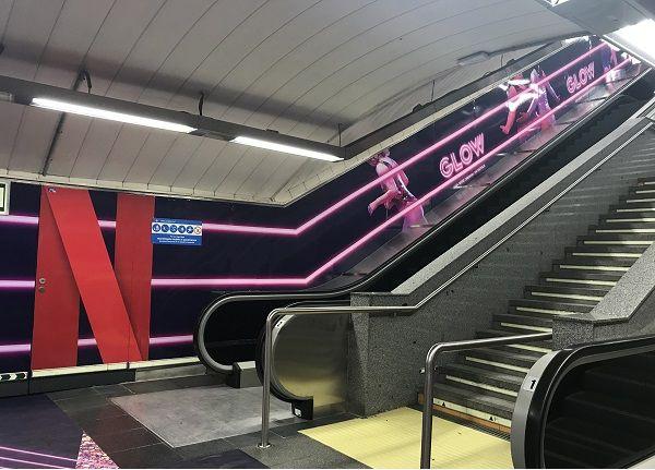 Escaleras de la estación de Chueca con la nueva campaña promocional de la serie GLOW | Fotografía: Somos Chueca
