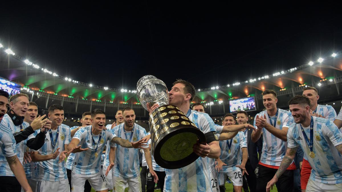 Messi besa el trofeo de la Copa América, mientras sus compañeros celebran.