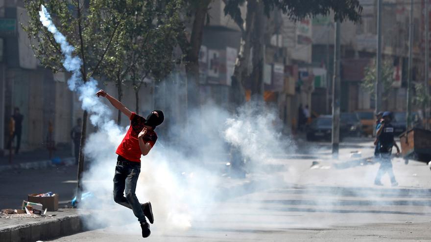 Un palestino devuelve una bomba de gas lacrimógeno lanzada por tropas israelíes durante enfrentamientos entre ambos en Hebrón (Palestina)
