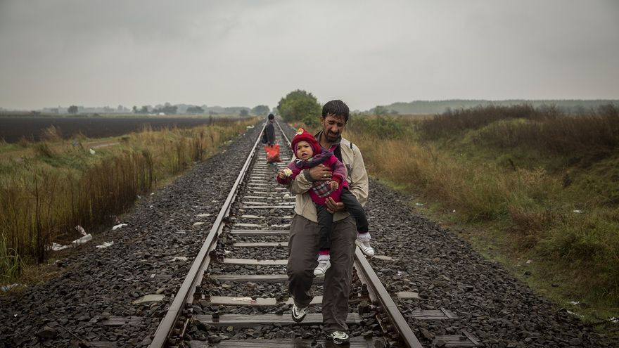 Supervivientes en busca de un refugio. Un padre camina por las vías del tren llevando a su hijo en brazos unos cientos de metros después de haber cruzado la frontera entre Serbia y Hungría. Roszke (Hungría) 10/09/2015. | FOTO: OLMO CALVO