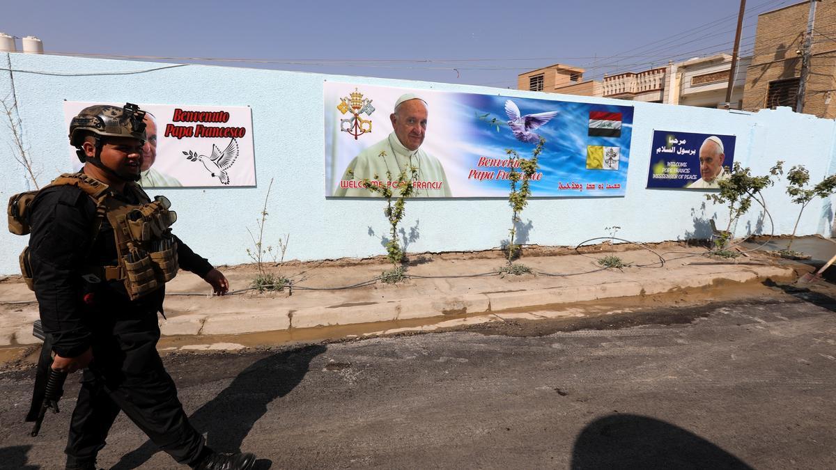 Un policía iraquí patrulla por una calle de Bagadad con carteles y murales alusivos a la visita del papa Francisco.EFE/EPA/AHMED JALIL
