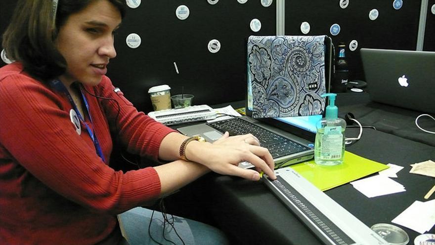 Una mujer invidente navega por internet con ayuda de su teclado Braille mientras escucha con su lector de pantallas