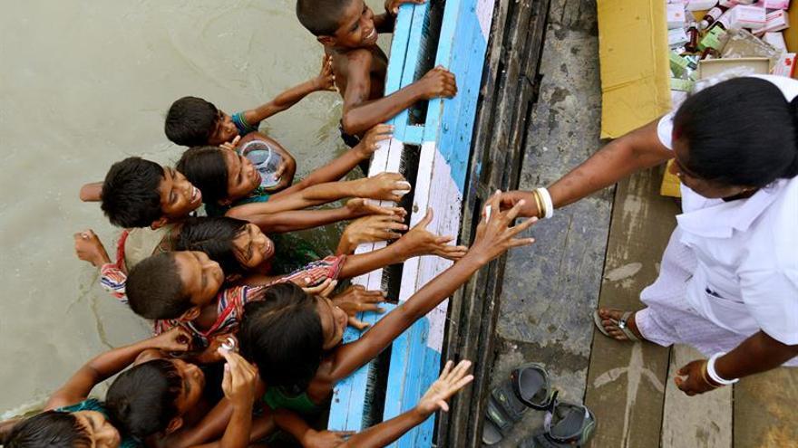 Niños afectados por las inundaciones recogen medicinas de un barco del Centro de Salud Público de Jhargaon en el distrito de Morigaon, en Assam (India).
