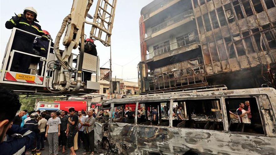 Los bomberos trabajan en el distrito de Karada en el centro de Bagdad, tra la explosión este domingo de un coche bomba.