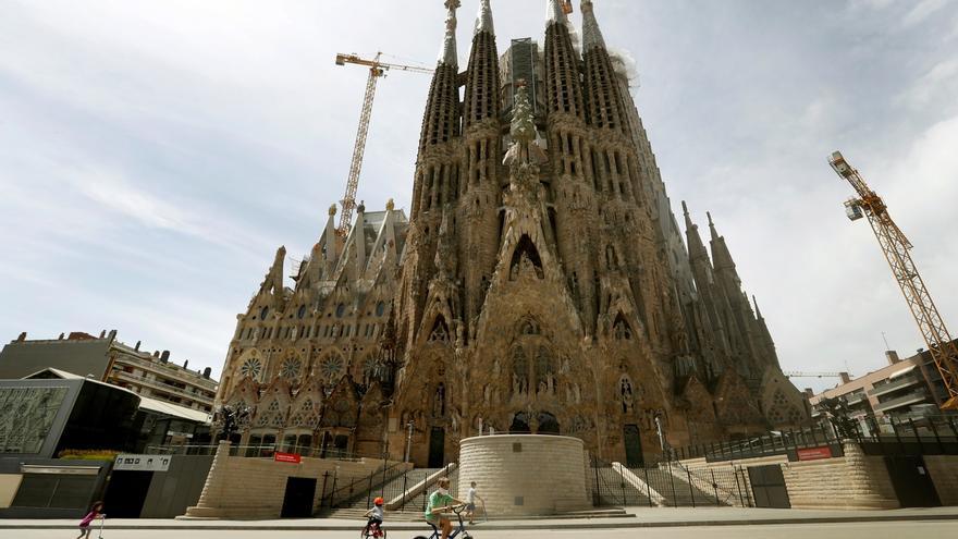 Varios niños juegan ante la Sagrada Familia de Barcelona.