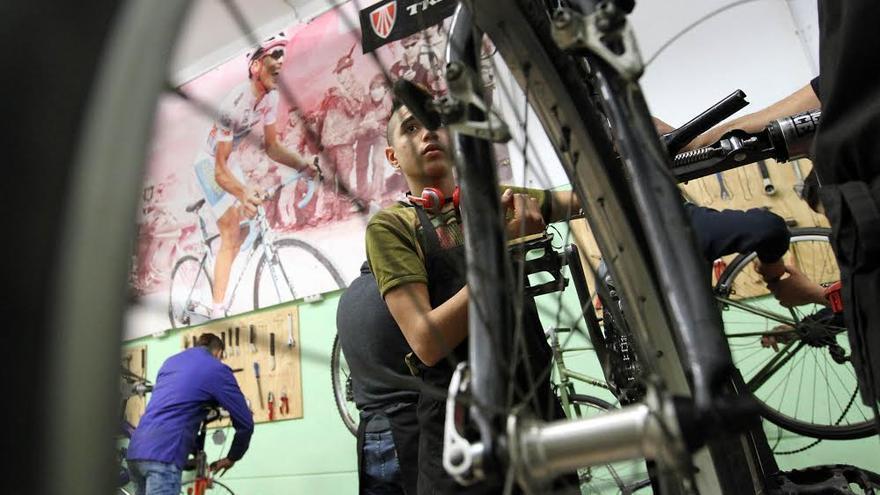 Uno de los jóvenes en un taller de reparación de bicicletas de Servei Solidari / Escola Pia Catalunya