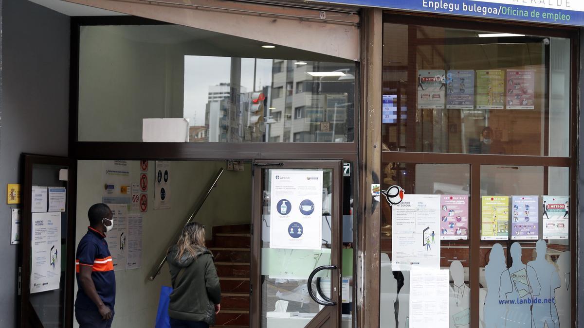 Dos personas hacen cola en una oficina de Lambide (empleo) en Bilbao donde se puede solicitar el ingreso mínimo vital (IMV).