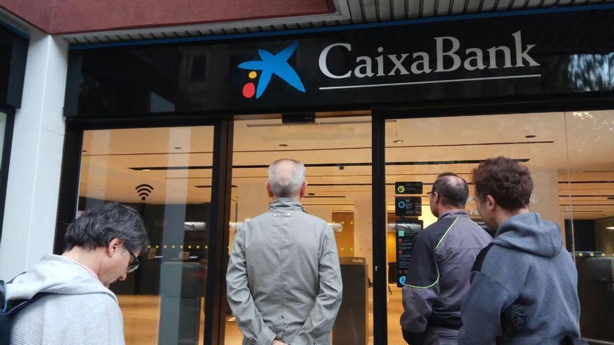 Cola ante una entidad de CaixaBanc en el Eixample de Barcelona