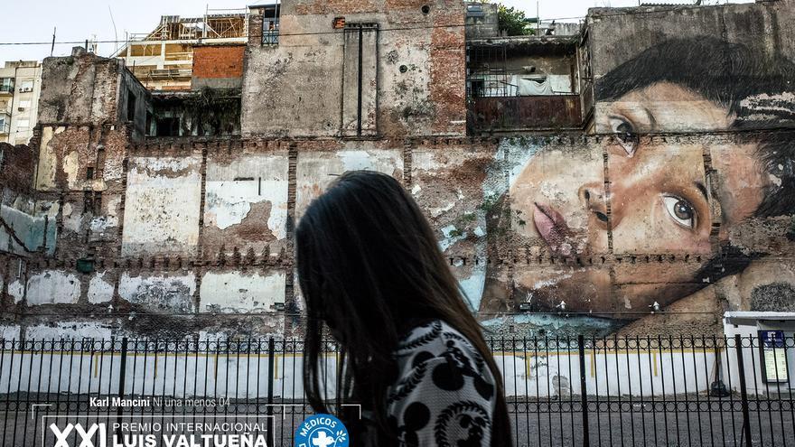 Buenos Aires. Una mujer camina en una calle del centro con un gran mural al fondo. Toda la ciudad está llena de paredes pintadas, a veces edificios enteros o calles. A menudo estas pinturas son políticas, muchas están en contra de la violencia de género, la injusticia y las personas desaparecidas. Foto: Karl Mancini. NI UNA MENOS. Segundo finalista.