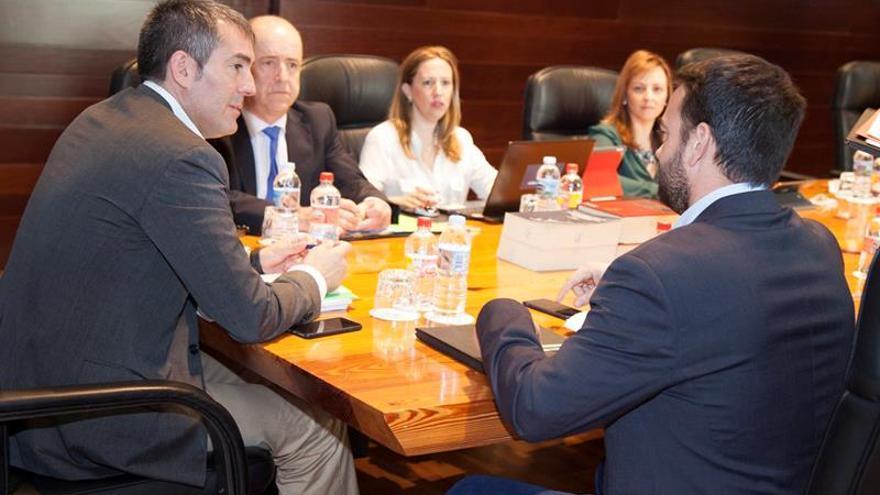El presidente del Gobierno de Canarias, Fernando Clavijo (i), conversa con el consejero de Presidencia, Aarón Afonso (d), momentos antes del Consejo de Gobierno del Ejecutivo canario celebrado el 18 de diciembre