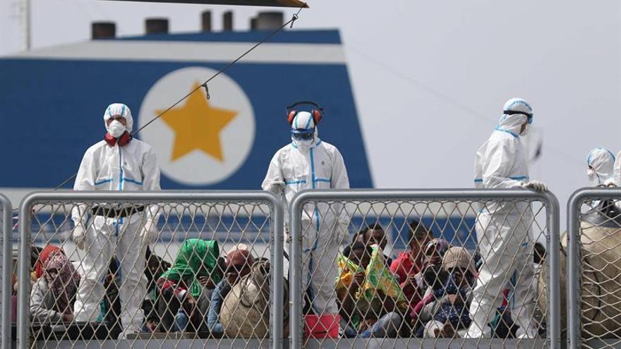 Trabajadores de los equipos de rescate se preparan para el desembarco de un grupo de unos 600 inmigrantes a su llegada al puerto de Nápoles (Italia), marzo de 2016.