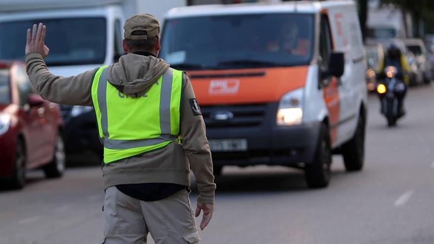 Un guardia civil detiene un vehículo de Unipost en L'Hospitalet, esta mañana.