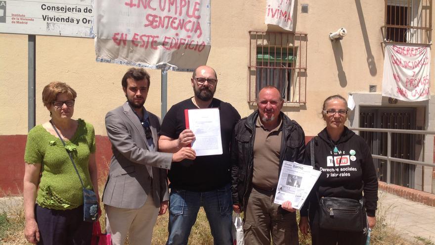 Vecinos de la Colonia Experimental de Villaverde Alto enseñan la sentencia que obliga a la rehabilitación de sus viviendas