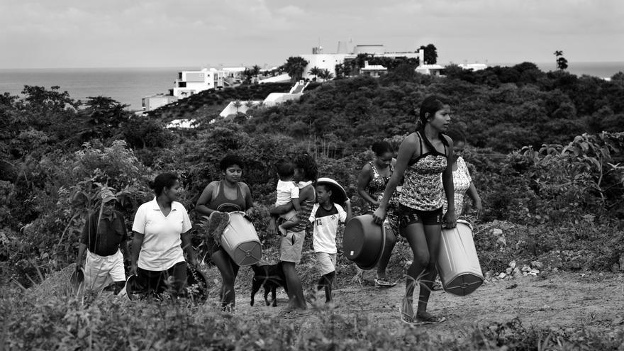Beneficiarias de la distribución realizada por Médicos Sin Fronteras (MSF)  caminan de vuelta hacia sus refugios; al fondo, se encuentra un resort de lujo de la zona turística de Muisne. Muchas de las familias afectadas en esta zona vivían principalmente de la pesca y del turismo antes del terremoto. Fotografía: Albert Masias/MSF