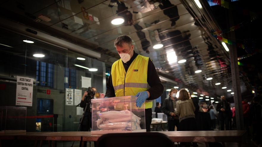 Un operario coloca las urnas, papeletas y demás material electoral en el Mercat del Ninot, de cara a las próximas elecciones catalanas del 14F en Barcelona, Cataluña