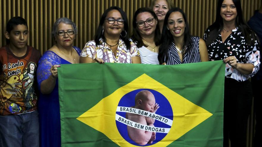 La ministra de Mujer, Familia y Derechos Humanos, en el centro, sostiene una bandera de Brasil con proclamas contra el aborto y las drogas.