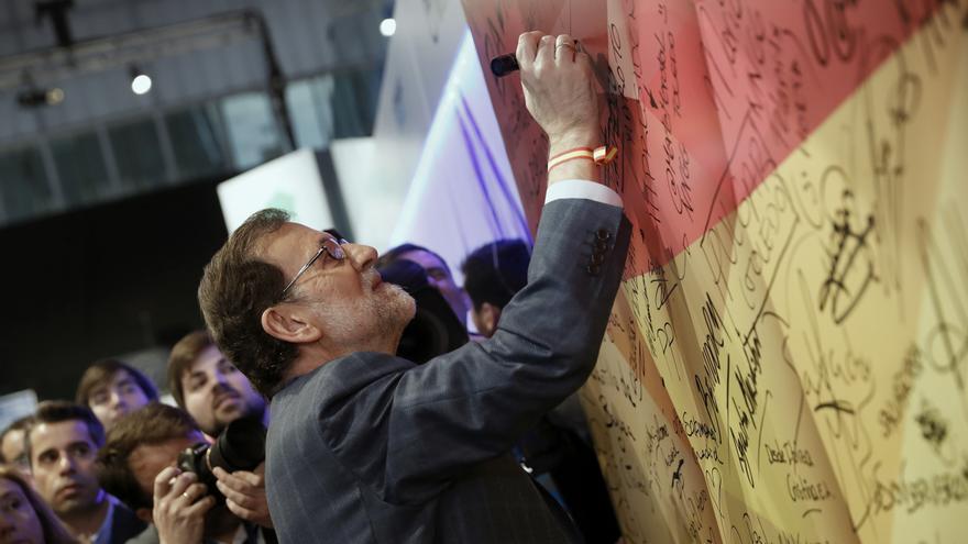 El presidente del Gobierno y líder del PP, Mariano Rajoy, firma en una bandera española a su llegada a la segunda jornada del XVIII Congreso nacional del partido en la Caja Mágica, el 11 de febrero de 2017