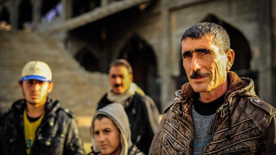 """Suleiman huyó de Sinjar con su familia en agosto. Atrás ha dejado sus pertenencias y también parte de su identidad, pues, al menos en las actuales condiciones, ya no se siente capacitado para dar clases. """"Vivo en esta mezquita en construcción con otras 70 personas. Hace muchísimo frío y es extremadamente húmedo. ¿Cómo es posible que estemos viviendo en un lugar  así?"""". / FOTO: Gabrielle Klein/MSF"""