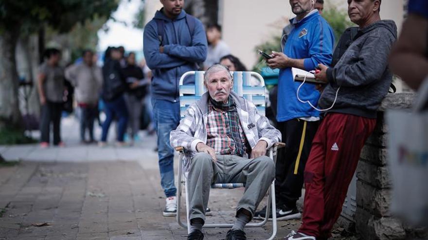 Adultos mayores esperan en fila para poder cobrar su jubilación en un Banco de San Justo, en la provincia de Buenos Aires (Argentina).