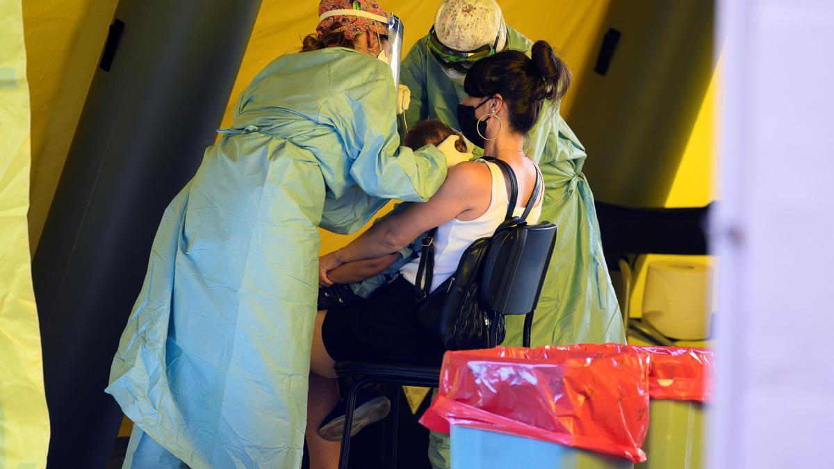 Personal sanitario realiza una prueba PCR a un niño en brazos de su madre