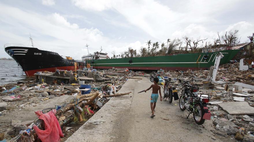 Un niño camina junto a un barco y varias casas destruidas por el tifón, junto a un depósito de combustible en la ciudad de Tacloban, en la provincia de Leyte, en el centro de Filipinas, el 11 de noviembre de 2013. AP /Aaron Favila