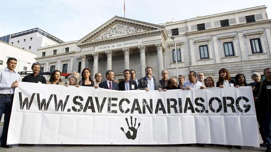 El presidente del Gobierno de Canarias, Paulino Rivero (6i), junto al coportavoz de Equo, Juan López de Uralde (8i), entre otros, durante su participación en un acto frente al Congreso de los Diputados, en contra de las prospecciones petrolíferas en aguas del archipiélago canario. Efe.