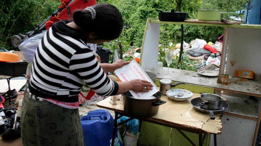 Mujer lavando platos cerca de un vertedero en el campo romaní de Noise-le-Grand, Francia, junio de 2012. © Amnesty International