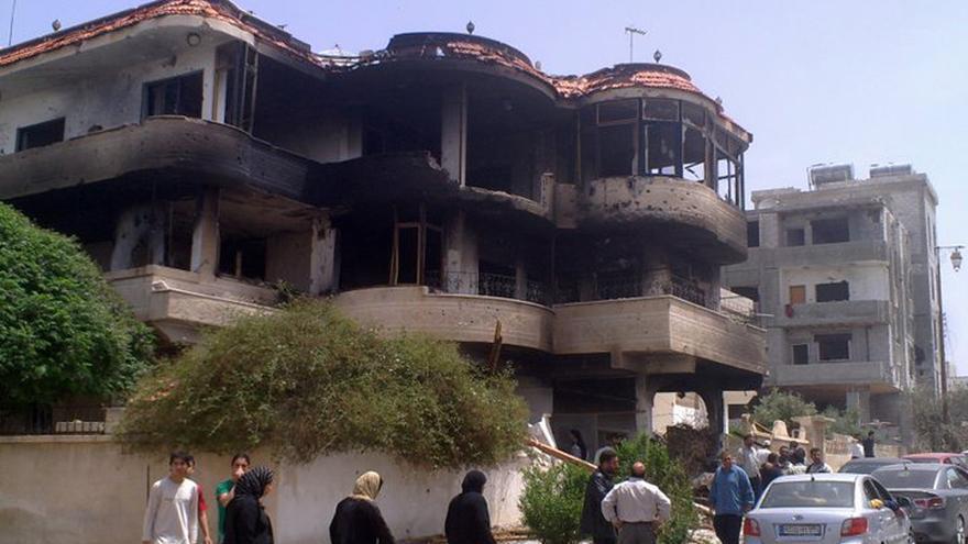 Un grupo de personas camina junto a unas viviendas destruidas en la ciudad siria de Daraa.