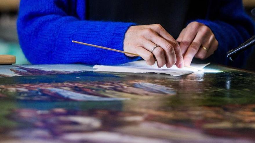 Imagen de archivo de una restauradora trabajando en un cuadro.