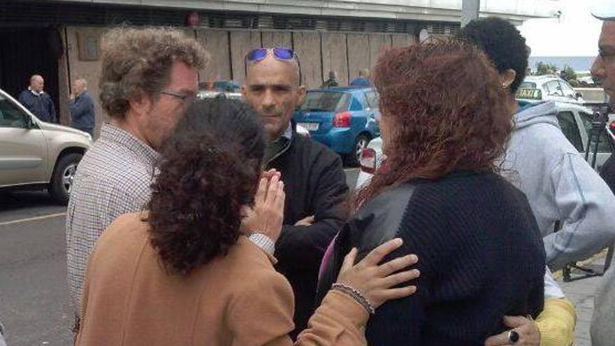 Rosa (de espaldas) y Juan, acompañados de miembros de Stop Desahucios, a la entrada a los Juzgados.