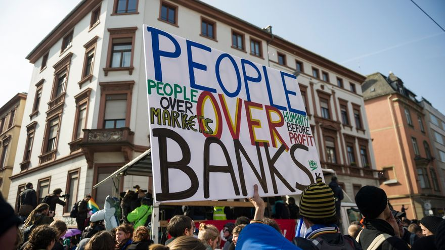 A protester holds a banner ''People over banks'' on the opening day of the European Central Bank (ECB) in Frankfurt am Main, western Germany, on March 18, 2015. Supporters of the so-called Blockupy alliance consisting of social movements, activists, workers, trade unions and parties are expected to stage large protests against austerity and the authority of the European Central Bank when the bank's new headquarters officially will be on March 18, 2015.