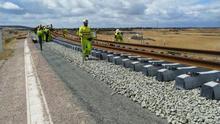 Un tren carrilero va dejando las vías sobre las traviesas