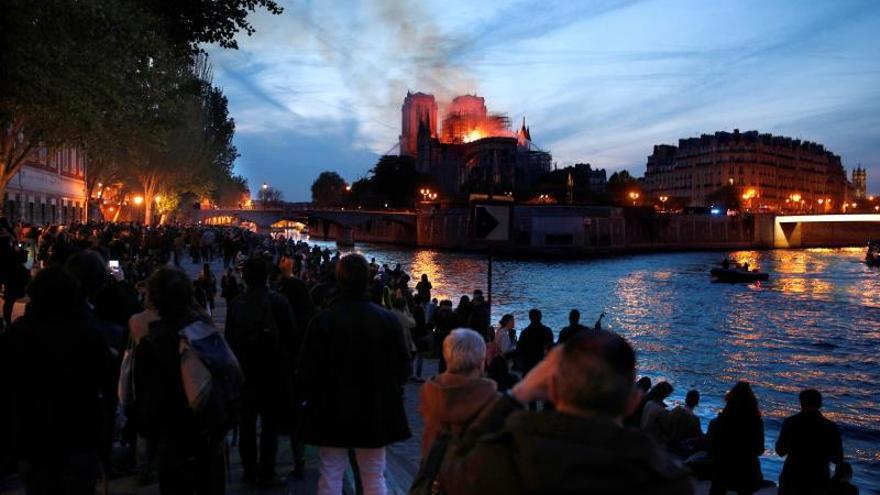 Decenas de personas en la orilla del río Sena observan la columna de humo y las llamas que consumen a la catedral de Notre-Dame. / EFE