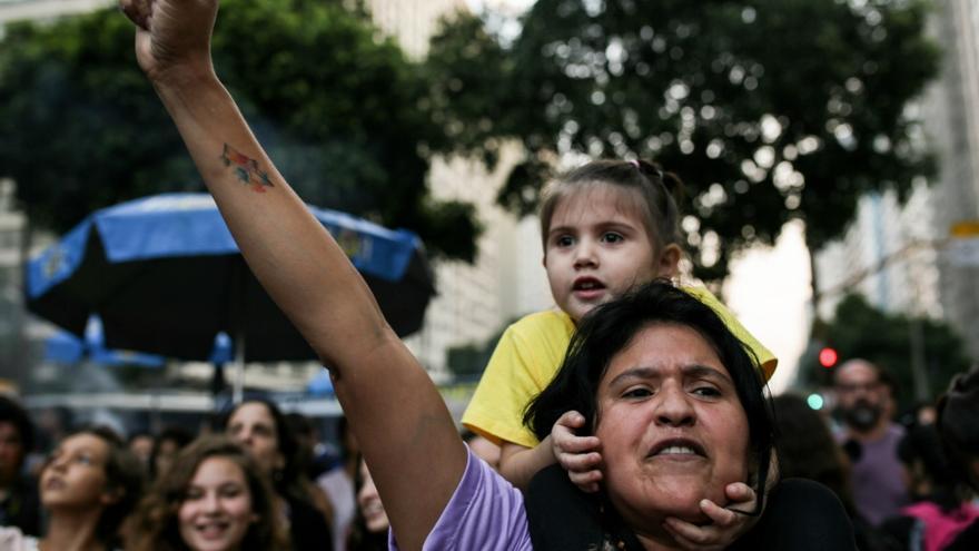 Manifestante con su hija a cuestas en la marcha feminista de Río ed Jaineiro, del 28 de mayo de 2016.