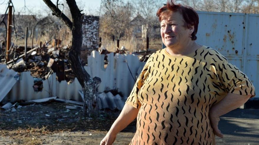 """Galina, de 64 años, se encuentra delante de la casa destruida de su vecino en Debaltsevo, una localidad de Donetsk golpeada duramente por el conflicto. Mientras las personas con recursos se han marchado a Rusia o a otras zonas de Ucrania, muchos como Galina siguen viviendo con el constante temor de ser bombardeados.   """"Nos escondimos en el sótano desde donde oíamos las explosiones muy cerca. Las bombas cayeron en nuestra calle e incendiaron la casa que se encuentra frente a la mía. Los bomberos no pudieron llegar porque el bombardeo causó  muchos otros incendios"""". Fotografía: Julie Rémy / MSF"""