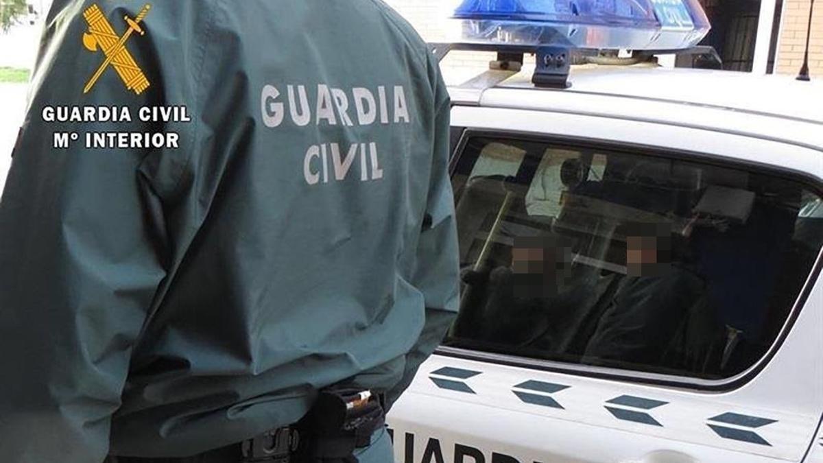 Archivo - Un agente de la Guardia Civil junto a un coche patrulla