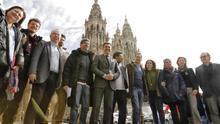 """De izquierda a derecha: el alcalde de Santiago, Xosé Sánchez Bugallo, (3i), el conselleiro de Cultura, Román Rodríguez, (6i) los actores Alex González (4i) y Verónica Echegui (9i), la comisaria del Xacobeo 21, Cecilia Pereira, (i) y parte del equipo de rodaje y de producción posan este viernes en la plaza del Obradoiro en Santiago de Compostela durante un descanso del rodaje de la serie """"3 Caminos""""."""