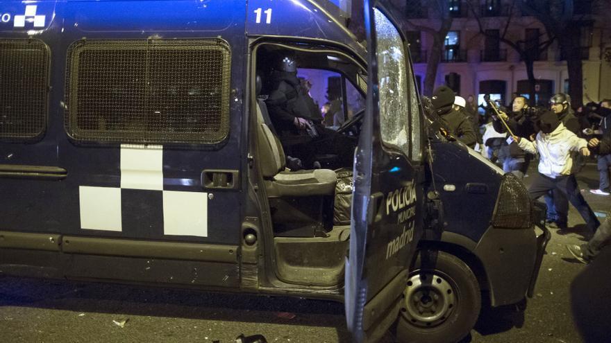 Un policía intenta sacar su arma cuando los manifestantes atacan su vehículo durante una protesta contra el gobierno en Madrid, España, Sábado, 22 de marzo 2014.  La policía y los manifestantes españoles se enfrentaron durante una manifestación contra la austeridad que atrajo a decenas de miles de personas al centro de Madrid el sábado.  La policía dijo en una declaración a seis agentes resultaron heridos y 12 personas fueron detenidas.  (AP Photo / Andres Kudacki)