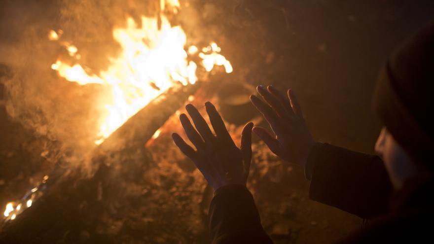 Un hombre se calienta las manos en el fuego dentro de un almacén abandonado en Belgrado, Serbia, el 5 de enero de 2017. | Foto: Marko Drobnjakovic / MSF