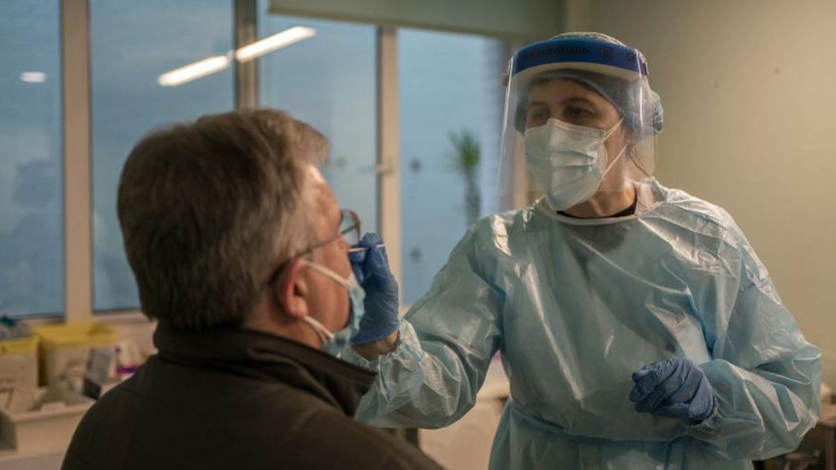 Una enfermera realiza un hisopado para PCR