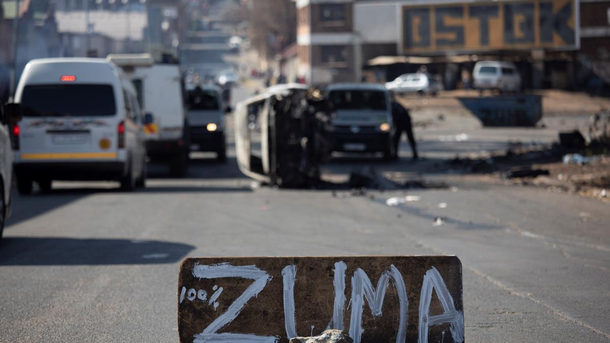 Un coche quemado en un bloqueo de carretera durante los enfrentamientos en Johannesburgo, Sudáfrica, este sábado.
